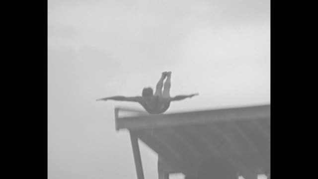 swimmers dive into pool for half-mile race / spectators in bleachers / swimmers turn at far end of pool / ralph flanagan swims final lap, touches... - diving platform stock videos & royalty-free footage