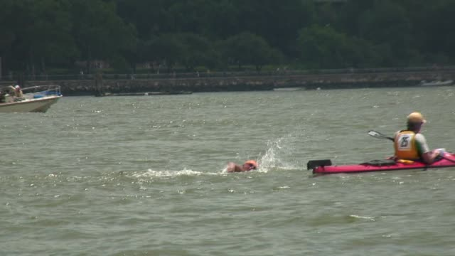 swimmers from around the world challenge themselves in the annual 30 mile circuit of manhattan island solo swimmer zoom out to show manhattan and... - salmini 個影片檔及 b 捲影像