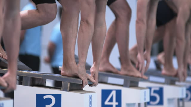 slo mo swimmers getting into their positions on starting blocks - the olympic games stock videos & royalty-free footage