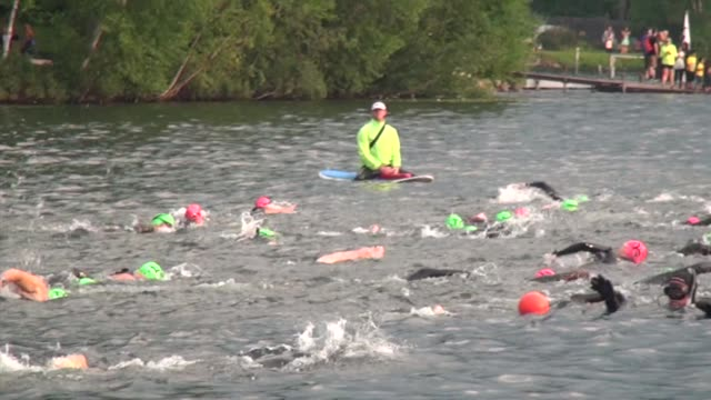 Swimmers head out in a lake in an Ironman Triathlon