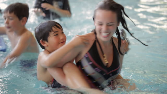 ha swimmers riding piggyback and playing in a pool / vancouver, british columbia, canada - swimming stock videos & royalty-free footage
