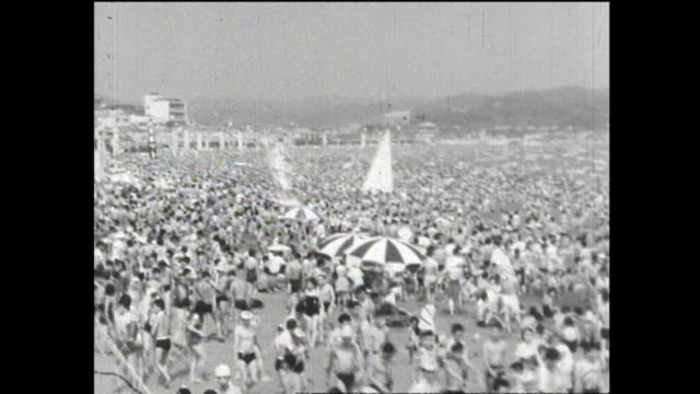 swimming beach swarming with people; crowds of climbers under the craze for mountaineering - 1950 1959点の映像素材/bロール