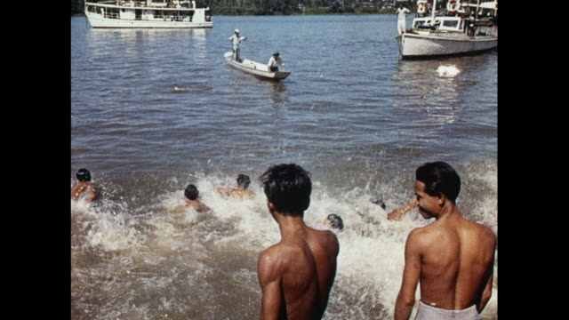 stockvideo's en b-roll-footage met montage swimming competition for duck prize on the river in sarawak - 1963