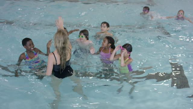 Swimming Instructor Giving High-Fives to Her Class in the Pool