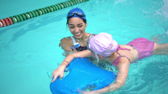 Swimming instructor teaching a little girl how to swim