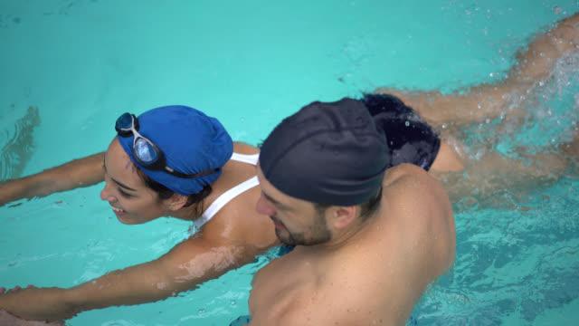 Zwemleraar onderwijzen een jonge persoon hoe te te zwemmen