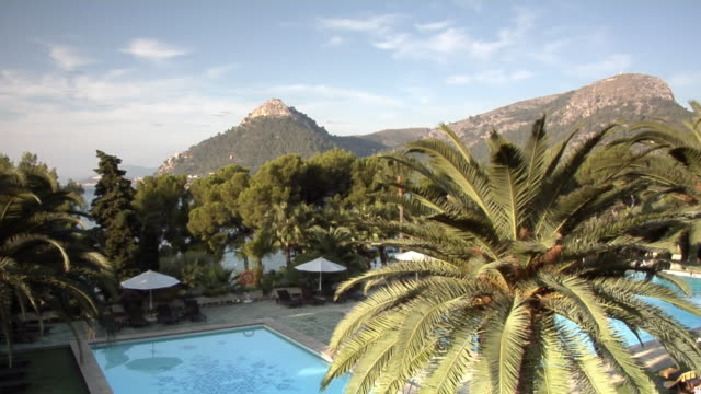 ms, ha, swimming pool and hills in background, formentor, majorca, spain - sonnenschirm stock-videos und b-roll-filmmaterial
