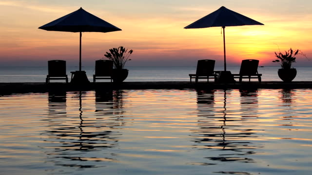 swimming pool sunset at a myamar beach with sun beds - tourist resort stock videos and b-roll footage
