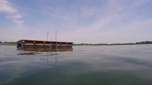 swimming towards a wooden pontoon. lake chiemsee, bavaria, germany - floating moored platform stock videos & royalty-free footage