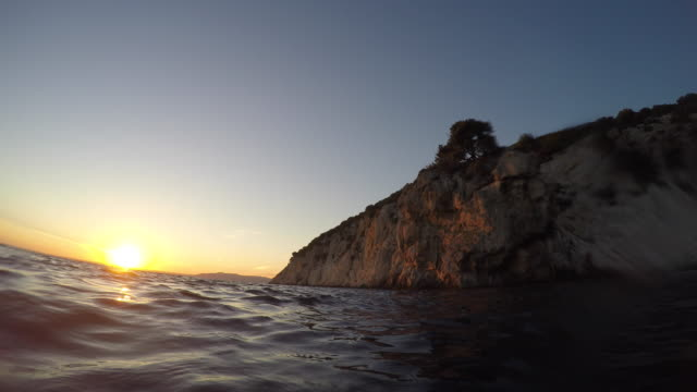 POV Swimming up to the sea surface at sunset