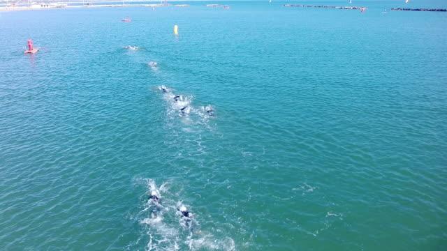 vídeos y material grabado en eventos de stock de swimminig_race_at_sea_from_above_w_drone-head_of_the_group - triatlón