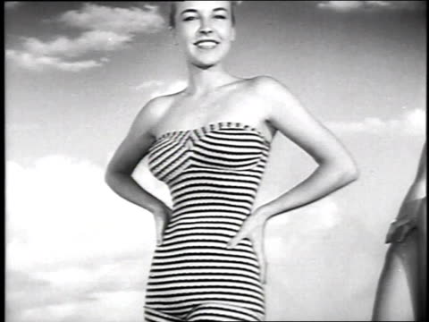 1951 MONTAGE Swimsuit models posing against painted backdrop and demonstrating suits / Hollywood, California, United States