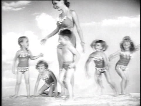 vídeos de stock, filmes e b-roll de 1951 montage swimsuit models posing against painted backdrop and demonstrating suits / hollywood, california, united states - roupa de natação