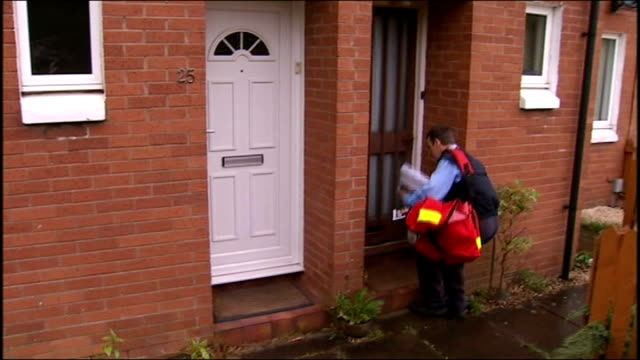 vídeos de stock, filmes e b-roll de leaflet campaign starts scotland edinburgh ext postal worker posting department of health leaflet on swine flu through letter box of residential... - gripe suína