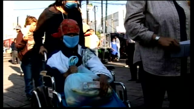 stockvideo's en b-roll-footage met swine flu continues to spread worldwide; mexico: mexico city: ext people queuing up outside hospital, some wearing face masks woman wearing face mask... - varkensgriep
