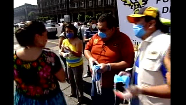 stockvideo's en b-roll-footage met emergency measures taken to tackle disease mexico mexico city low angle shot people wearing face masks along men handing out face masks people... - varkensgriep