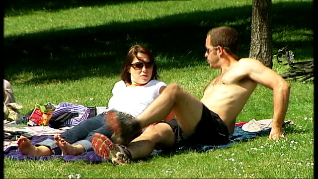 stockvideo's en b-roll-footage met latest cases in england / global spread of disease; ext good shots showing people walking and sitting in park on a sunny spring day including some... - varkensgriep