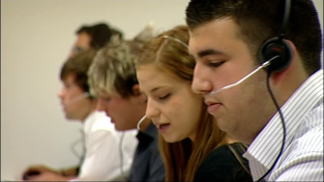 stockvideo's en b-roll-footage met nhs national pandemic flu service call centre various of staff seated at computers speaking to callers on telephone headsets - varkensgriep