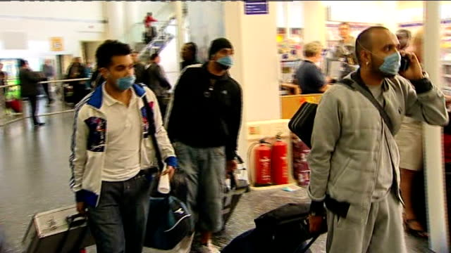 stockvideo's en b-roll-footage met results of independent review published; 2009 england: int * * beware flash photography * * travellers arriving at airport wearing face masks - varkensgriep
