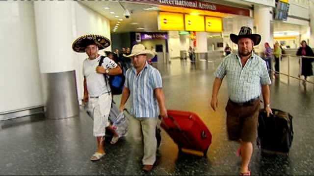 stockvideo's en b-roll-footage met two cases confirmed in scotland england gatwick airport int british holidaymakers wearing mexican hats along through arrivals lounge close shots of... - varkensgriep
