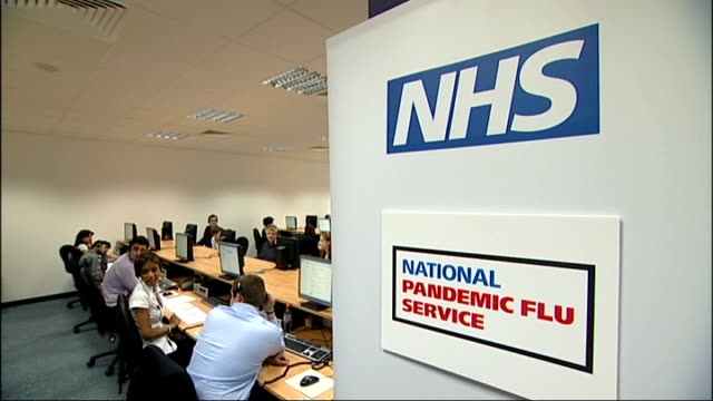 stockvideo's en b-roll-footage met swine flu vaccine take-up concerns; 2009 boxes of tamiflu drugs opened national pandemic flu service call centre workers seated at computers needle... - varkensgriep
