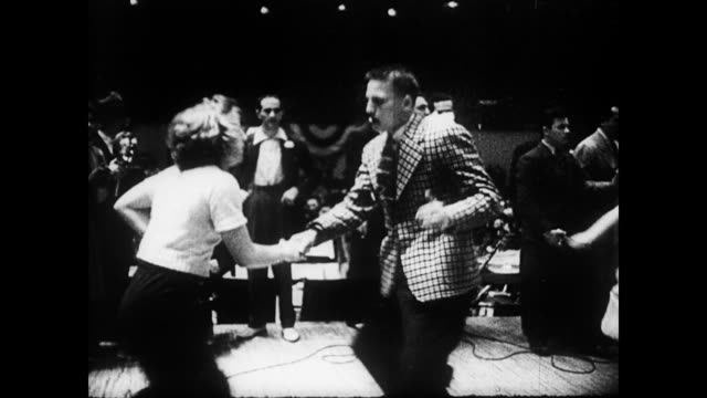 / swing dance contest with men and women dancing until they drop / man resisting judges as they try to escort him from the floor before he collapses... - 1940 bildbanksvideor och videomaterial från bakom kulisserna