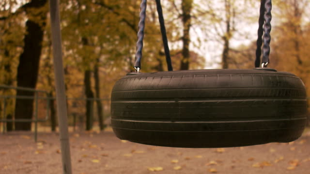 a swing in movement in a park sweden. - tyre swing stock videos & royalty-free footage