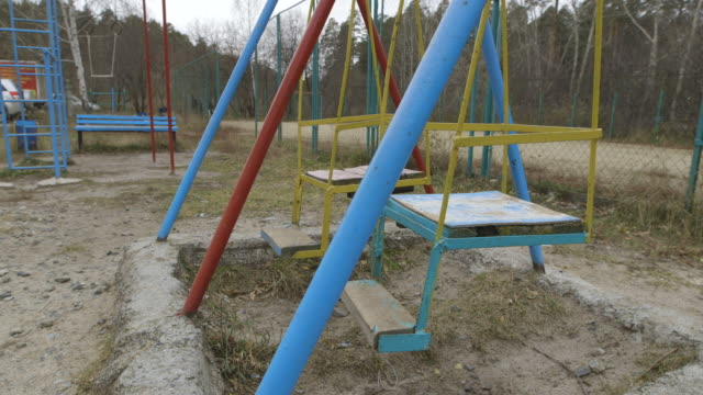 swing set on playground in asbest, russia - parco giochi video stock e b–roll