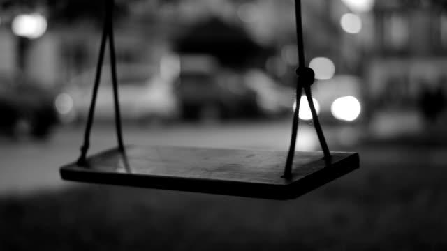 スインギングスイング、通り過ぎる車を背景にした、白黒 - 黒点の映像素材/bロール