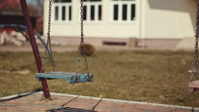 stockvideo's en b-roll-footage met slingerende schommels op lege school of parkspeelplaats. stock video - schommelen bungelen