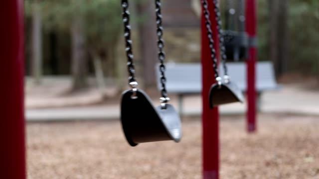 stockvideo's en b-roll-footage met swingende schommels op lege school of park speeltuin. - schommelen bungelen