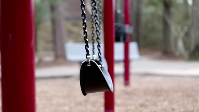 vídeos de stock e filmes b-roll de swinging swings on empty school or park playground. - public park