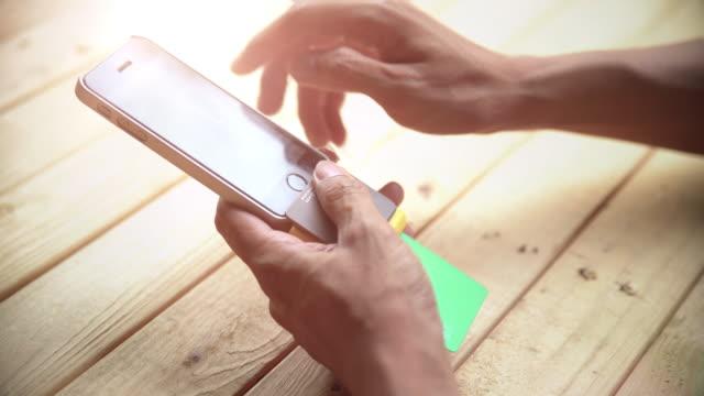 vídeos de stock e filmes b-roll de deslizar um cartão de crédito - vendedor trabalho no comércio