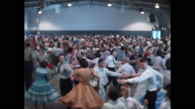 vídeos de stock e filmes b-roll de swirl of square dancers wide view of entire dancing crowd in dance hall - dança quadrada