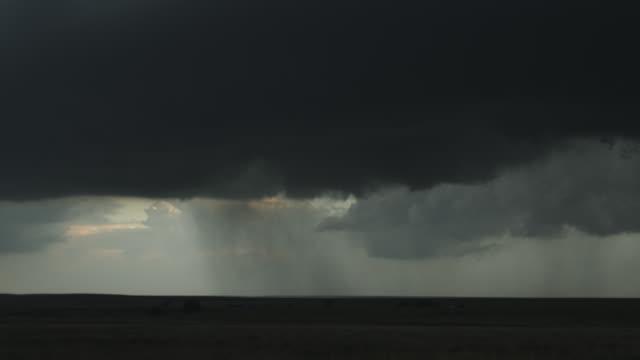 stockvideo's en b-roll-footage met swirling thunderstorm with updraft base spilling rain over prairie farmland, time lapse - artbeats
