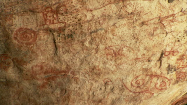 swirling written symbols cover a cave wall at pedra pintada cave in brazil. available in hd. - roraima state stock videos and b-roll footage