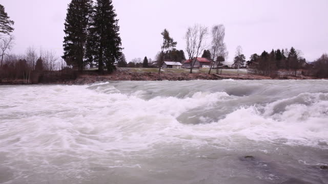 Swirls in the river Lech  flowing  through the village in a snowy wintertime day.