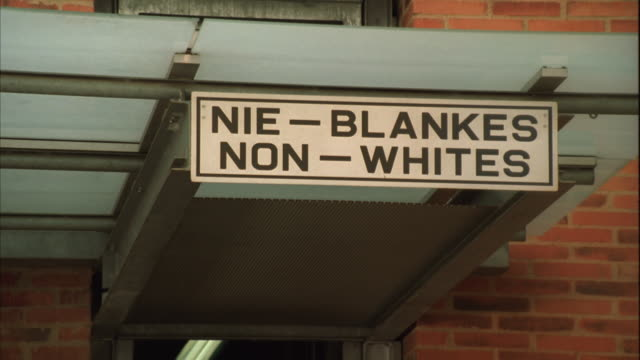 "swish pan and zoom out of signs above the entrances of the apartheid museum, in afrikaans and english, one saying ""whites"" the other ""non-whites"" - apartheid stock videos and b-roll footage"