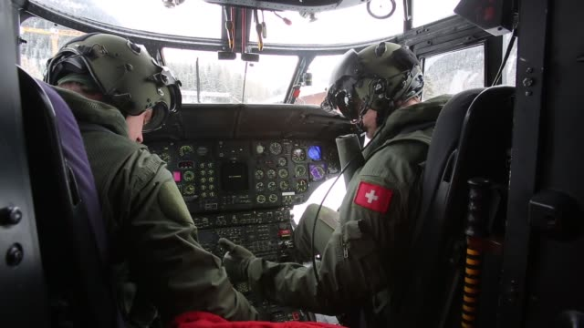 vídeos de stock, filmes e b-roll de swiss air force pilots preparing for take off in cockpit of helicopter during security preparations ahead of the 2013 world economic forum includes... - 2013