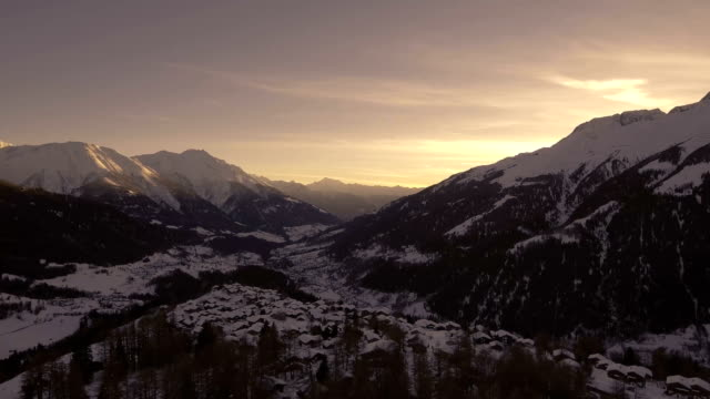 Swiss Alpine village and mountains at sunset