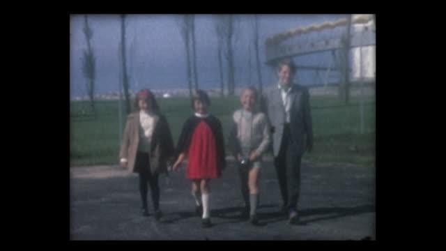 1964 swiss expo 64 kids walk to camera - utställning bildbanksvideor och videomaterial från bakom kulisserna