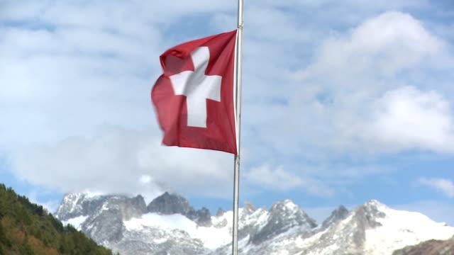 stockvideo's en b-roll-footage met swiss flag flutters in the wind, mountain range in background. - plusteken