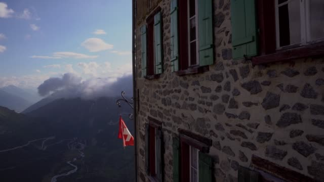 swiss flag flutters on building in the wind - flag blowing in the wind stock videos & royalty-free footage