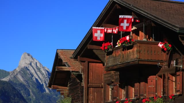 swiss flags on a traditional swiss chalet on august 7 2020 in gstaad switzerland gstaad is known in high society circles for being a posh ski resort... - stereotypically upper class stock videos & royalty-free footage