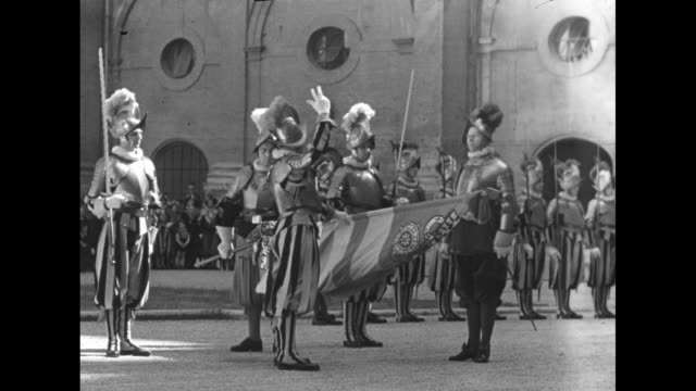 swiss guard officers standing in row looking on / cardinal and guardsman standing in front of row of guardsman / guardsmen standing in row present... - swiss guard stock videos and b-roll footage
