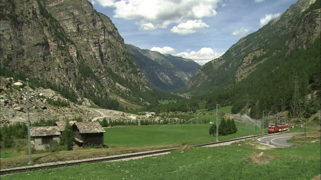 A Swiss mountain train comes running through the valley