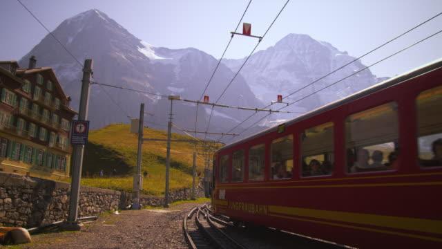 swiss railcar full of passengers passes hotel - berner alpen stock-videos und b-roll-filmmaterial