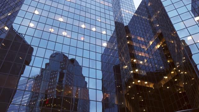 vídeos de stock, filmes e b-roll de vídeo giratório panorâmico de um exterior de edifício de escritório de vidro de montreal com reflexos - panning
