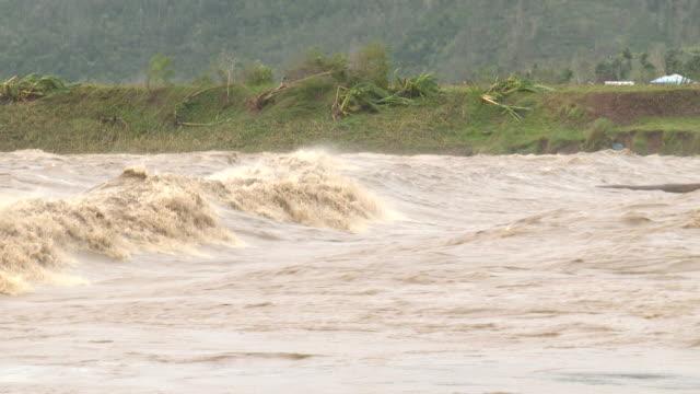 vídeos de stock e filmes b-roll de swollen fast flowing river in philippines as typhoon koppu hit on 18th october 2015 - filipinas