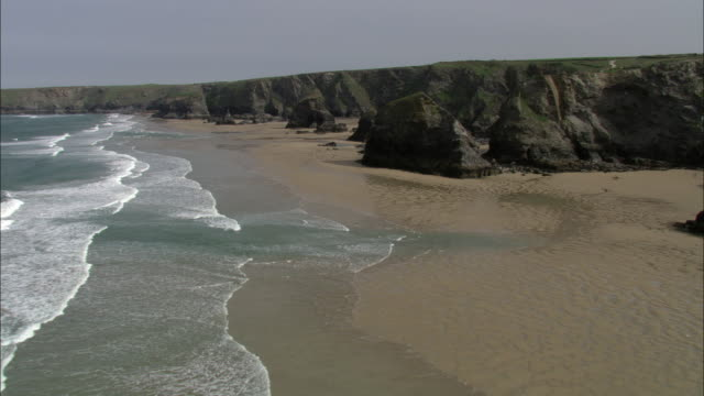 swooping aerial over cliffs, beach and sea, cornwall, uk - cliff stock videos & royalty-free footage